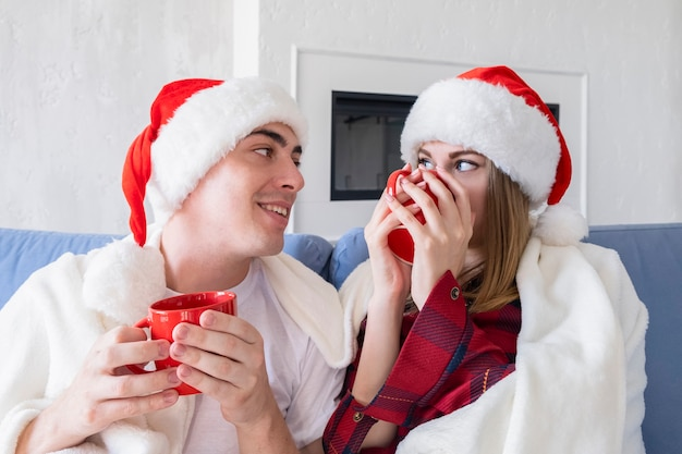 Christmas at home concept. profile side view photo of two lovely, carefree persons sitting on cozy couch or sofa in living room holding red cups looking to each other with smile