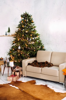 크리스마스 트리, 소파, 촛불과 장식이있는 테이블로 장식 된 소파가있는 크리스마스 홈 인테리어.