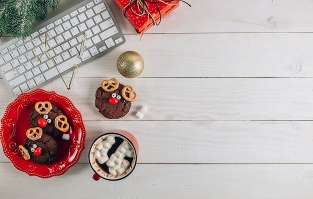 Christmas home office desk with computer, cookies, cup of coffee and christmas gold decorations