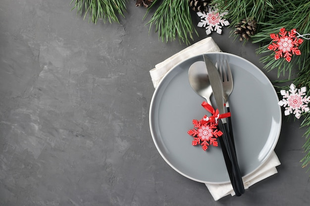 Christmas home table setting with gray plate and wooden snowflakes on gray table. top view. stay home. space for text