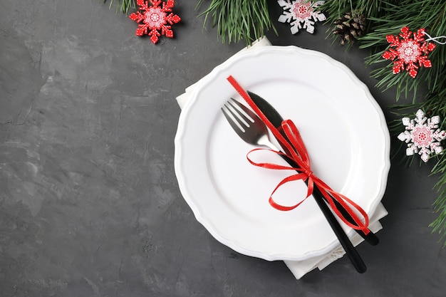 Christmas home table setting with white plate and wooden snowflakes on gray table. top view. stay home. space for text