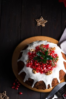 Christmas homebaked chocolate cake decorated with white icing and pomegranate kernels on a wooden dark , flat lay
