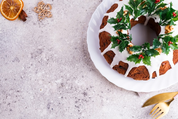 Christmas homebaked dark chocolate bundt cake decorated with holly berry branches on stone