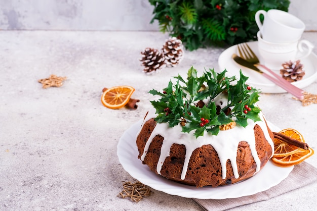 Christmas homebaked dark chocolate bundt cake decorated with white icing and holly berry branches close-up