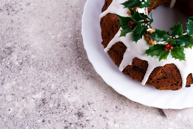 Christmas homebaked dark chocolate bundt cake decorated with white icing and holly berry branches a light concrete . flat lay