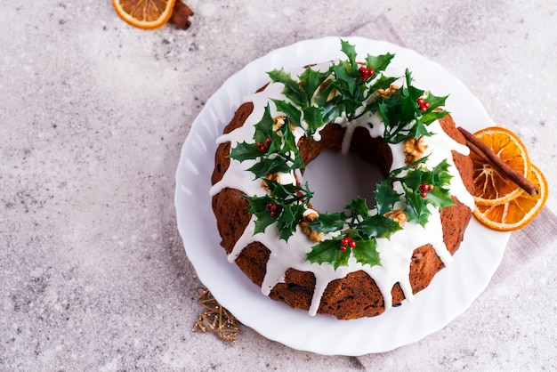 Christmas homebaked dark chocolate bundt cake decorated with white icing and holly berry branches on a light concrete . flat lay