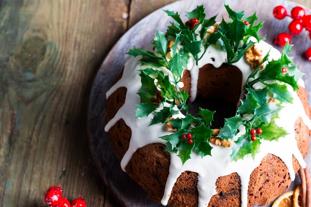 Christmas homebaked dark chocolate bundt cake decorated with white icing and holly berry branches a rustic old wooden , top view