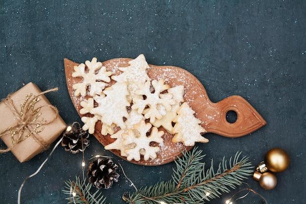ツリーと雪片の形でクリスマスの自家製ベーキングクッキー