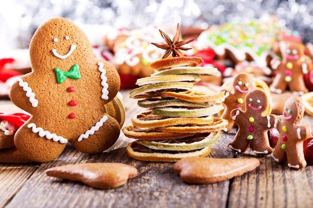 나무 테이블에 말린 과일로 만든 크리스마스 홈메이드 진저브레드 쿠키와 크리스마스 트리