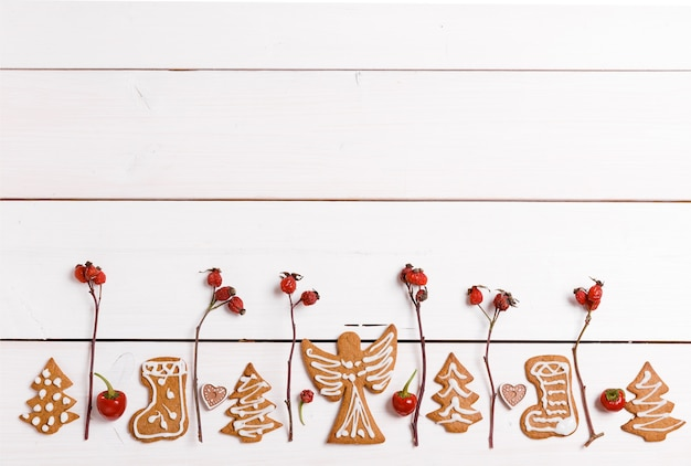 Рождественские домашние пряники и красные ягоды шиповника, на белом деревянном столе. рождественский баннер. т