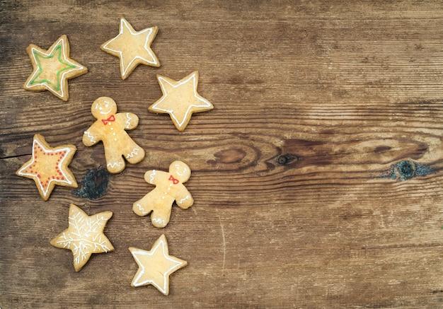 Рождественские домашние пряники человека и звезд на деревенском деревянном фоне, вид сверху