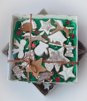 ボックスに白い背景の上のクリスマスの自家製ジンジャーブレッドクッキー新年の贈り物