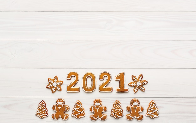 Christmas homemade gingerbread cookies in the shape of a masked man and numbers of new year on white wooden table, , top view, copy space