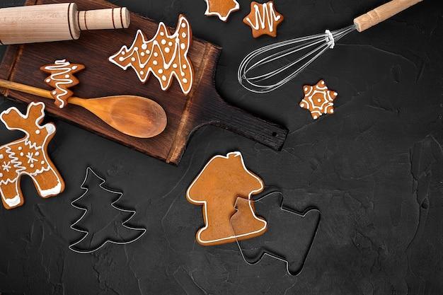 Рождественские домашние пряники со специями и разделочная доска на темном фоне с копией пространства f ...