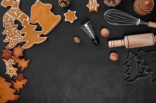 크리스마스 홈메이드 진저브레드 쿠키, 향신료 및 커팅 보드는 텍스트 위쪽 보기를 위한 복사 공간이 있는 어두운 배경입니다. 휴일, 축하 및 요리 개념입니다. 새 해와 크리스마스 엽서