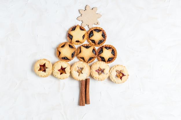 Рождественские домашние пироги с фаршем в виде елки на белом фоне цемента