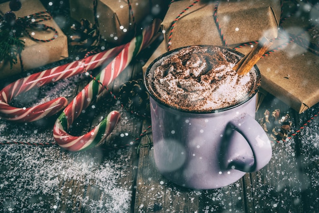 Christmas , hot chocolate or cocoa with whipped cream and spices, christmas gifts, candy canes, christmas tree branch and pine cones, on old rustic wooden table with snow, copyspace toned