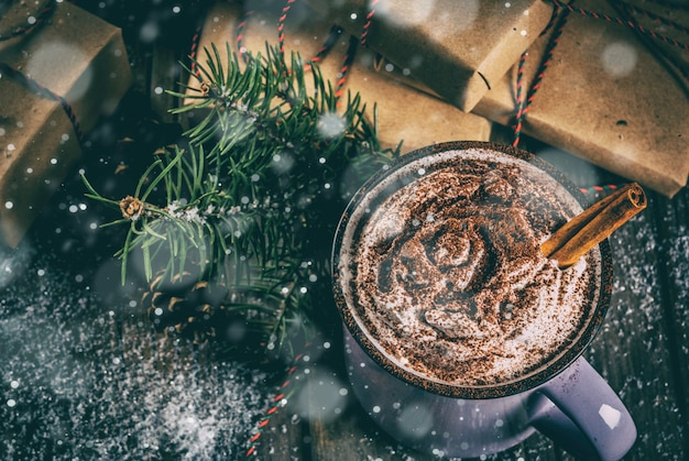 Christmas , hot chocolate or cocoa with whipped cream and spices, christmas gifts, candy canes, christmas tree branch, pine cones, old rustic wooden table with snow, copyspace top view toned