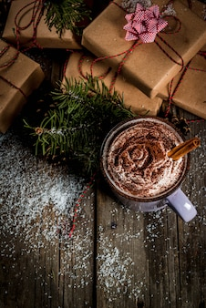 Christmas , hot chocolate or cocoa with whipped cream and spices, christmas gifts, candy canes, christmas tree branch, pine cones, old rustic wooden table with snow, copyspace top view