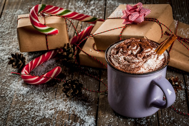 Christmas , hot chocolate or cocoa with whipped cream and spices, christmas gifts, candy canes, christmas tree branch and pine cones, on old rustic wooden table with snow, copyspace