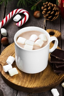 Christmas hot chocolate drink with cream and marshmallows on a wooden surface