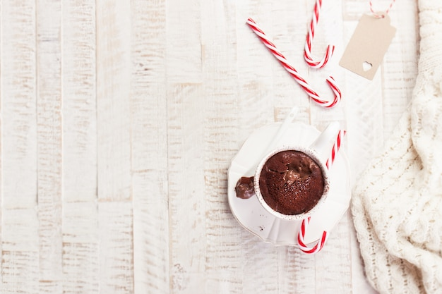 Christmas hot chocolate with cacao and candy cane, top view with copy space