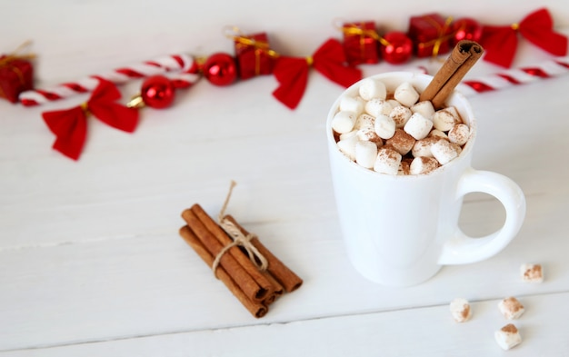 Christmas hot chocolate with marshmallows, christmas toy peppermint candy cane at mug, copy space.