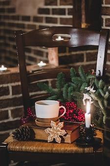 木製のキャンドルと古いセラミックマグカップのミニマシュマロとクリスマスホットチョコレート。