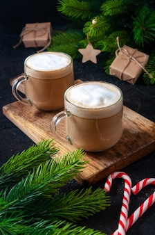 Christmas hot drink. cocoa coffee or chocolate in glasses on dark table with candy, gift box and branches fir tree.