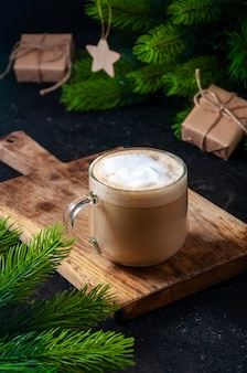 크리스마스 뜨거운 음료. 선물 상자와 분기 전나무 나무와 어두운 테이블에 안경에 코코아 커피 또는 초콜릿.
