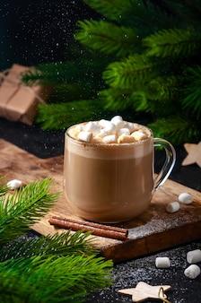 Рождественский горячий напиток. какао-кофе или шоколад в очках с зефиром и просеиванием сахарной пудры на темном столе.