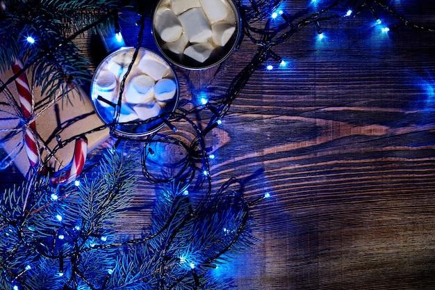 크리스마스 따뜻한 음료. 나무 배경에 마시멜로, 선물 상자, 크리스마스 조명, 화환, 가문비나무 가지가 있는 코코아. 평면도. 공간을 복사합니다. 플랫 레이. 정물. 모형