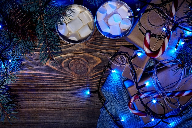 Christmas hot drink. cocoa with marshmallow, gift box, christmas lights, garland and spruce branches on a wooden background. top view. copy space. flat lay. still life. mock-up