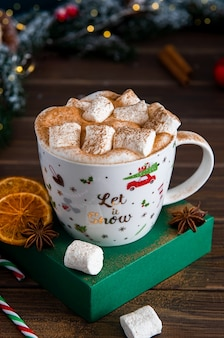 Christmas hot drink with marshmallows and spices on a background of snowy fir branches