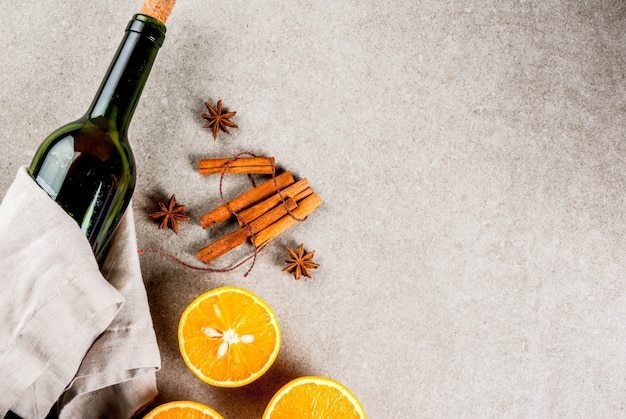 Christmas hot drinks recipes, set of ingredients for mulled wine: wine bottle, spices, orange