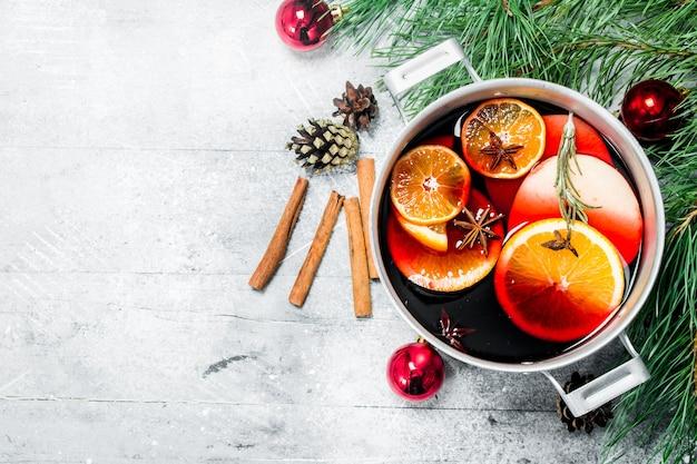 Рождественский горячий глинтвейн в горшочке со специями и зеленью. на деревенском столе.