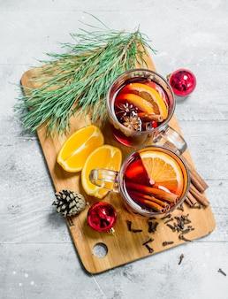 향기로운 향신료와 함께 크리스마스 뜨거운 mulled 와인. 소박한 배경.