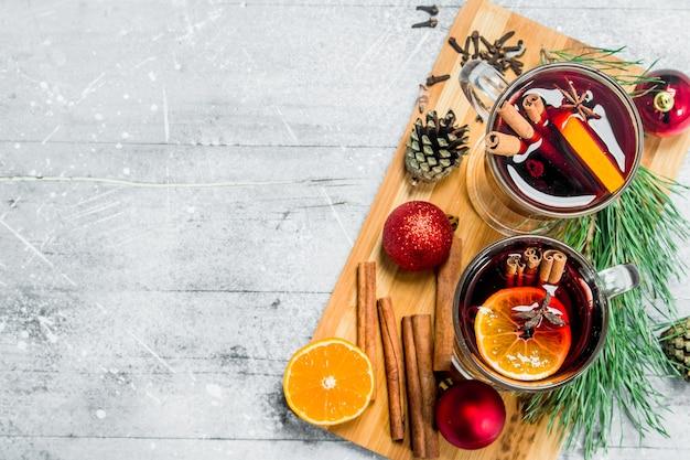 香辛料入りのクリスマスホットホットワイン。素朴な背景に。