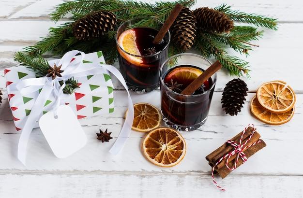 Рождественский горячий глинтвейн с корицей, кардамоном и анисом на белом деревянном фоне, новогодняя открытка