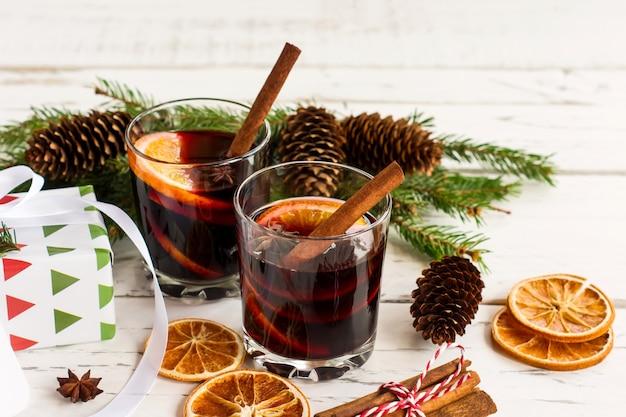 Горячий глинтвейн рождества с кардамоном корицы и анисом на белой деревянной предпосылке, поздравительной открытке нового года.