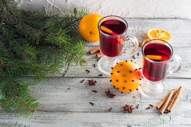 나무가 있는 흰색 나무 배경에 계피 오렌지와 아니스를 곁들인 크리스마스 핫 멀드 와인