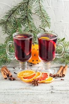 나무가 있는 흰색 나무 배경에 계피 오렌지와 아니스를 곁들인 크리스마스 뜨거운 mulled 와인