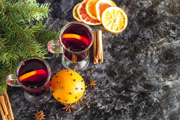 Christmas hot mulled wine with cinnamon orange and anise on dark background with tree