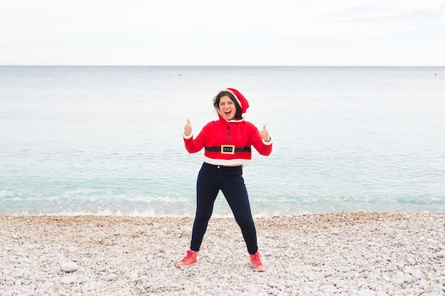 Christmas, humor and people concept - young happy woman in santa claus suit at the beach showing thumbs up near the sea.
