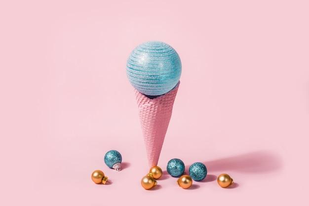 青と金のボールとクリスマスのアイスクリームコーン。最小限の休日の概念。