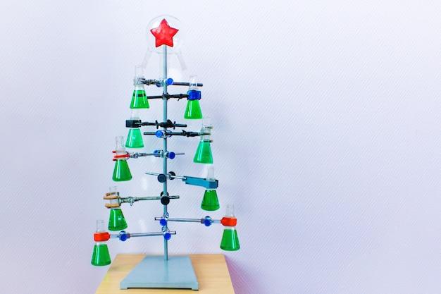 化学実験室でのクリスマス。カラフルな液体のフラスコから自家製のクリスマスツリー