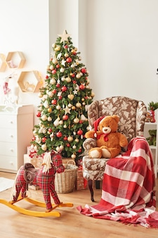 Christmas interior of children's bedroomchristmas in the nursery. rocking horse and soft toy bear on background of christmas tree.