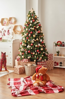 Christmas interior of children's bedroomchristmas in the nursery. soft toy bear on background of christmas tree