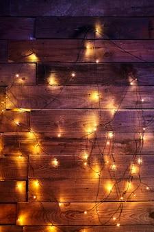 クリスマスの室内装飾。木製の背景に明るく輝くガーランド。黄色の新年の電球