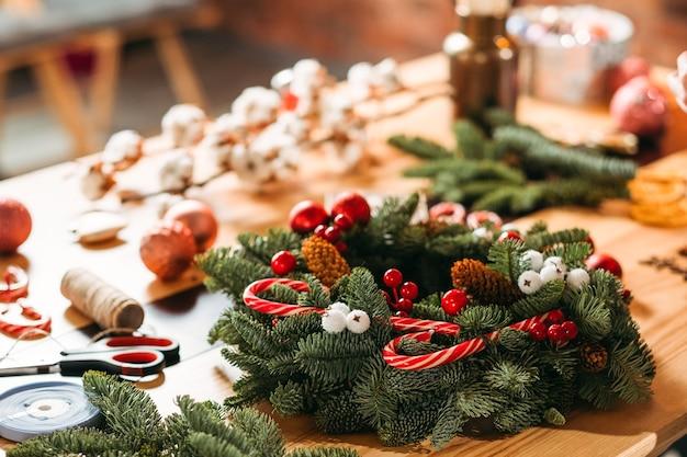 크리스마스 인테리어 장식. 플로리스트 워크샵. 지저분한 직장에 전나무 나무 화 환